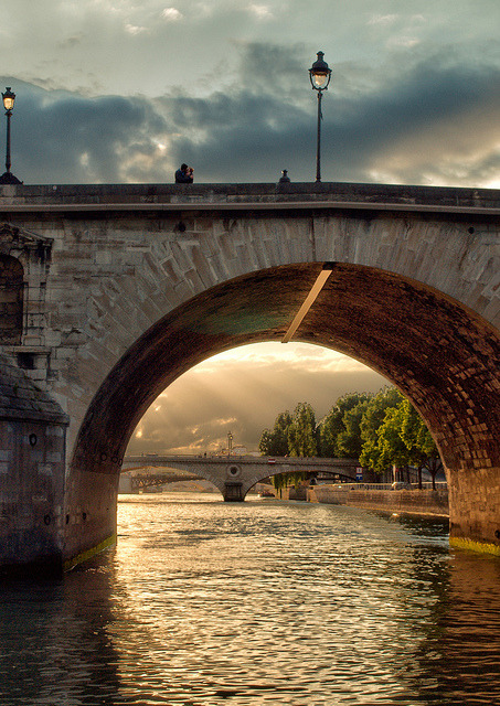 A kiss on a bridge over the River Seine, Paris, France